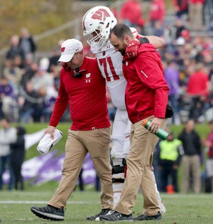 Wisconsin offensive tackle Cole Van Lanen is helped off the first after suffering a left leg injury against Northwestern during the first half Saturday.