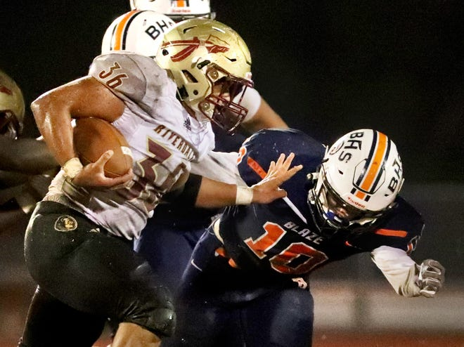 Riverdale's Drew Smith (36) runs the ball as Blackman's Matthew Hall (10) moves in to tackle Smith during a game Oct. 26. Both teams begin postseason play this week.