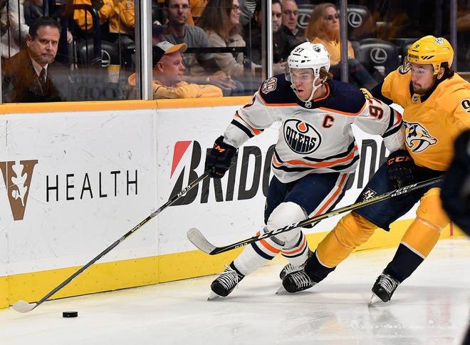 Predators left wing Filip Forsberg (9) tries to get the puck from Oilers center Connor McDavid (97) during the first period at Bridgestone Arena Saturday, Oct. 27, 2018, in Nashville, Tenn.