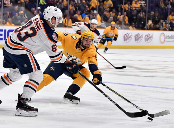 Predators left wing Filip Forsberg (9) tries to get the puck from Oilers defenseman Matt Benning (83) during the first period at Bridgestone Arena Saturday, Oct. 27, 2018, in Nashville, Tenn.