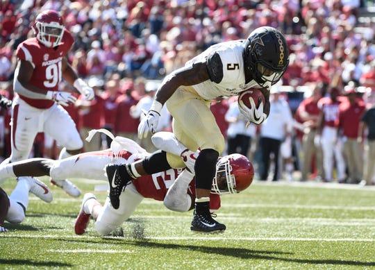 Vanderbilt running back Ke'Shawn Vaughn slips past Arkansas defender Kamren Curl to score a touchdown in the second half of an NCAA college football game Saturday, Oct. 27, 2018, in Fayetteville, Ark.