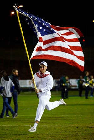 Independence senior Justin Marcus runs with the U.S. flag before their game against Ravenwood on Oct. 26 in Thompson's Station. Independence will take on Smyrna at 7 p.m. Friday.
