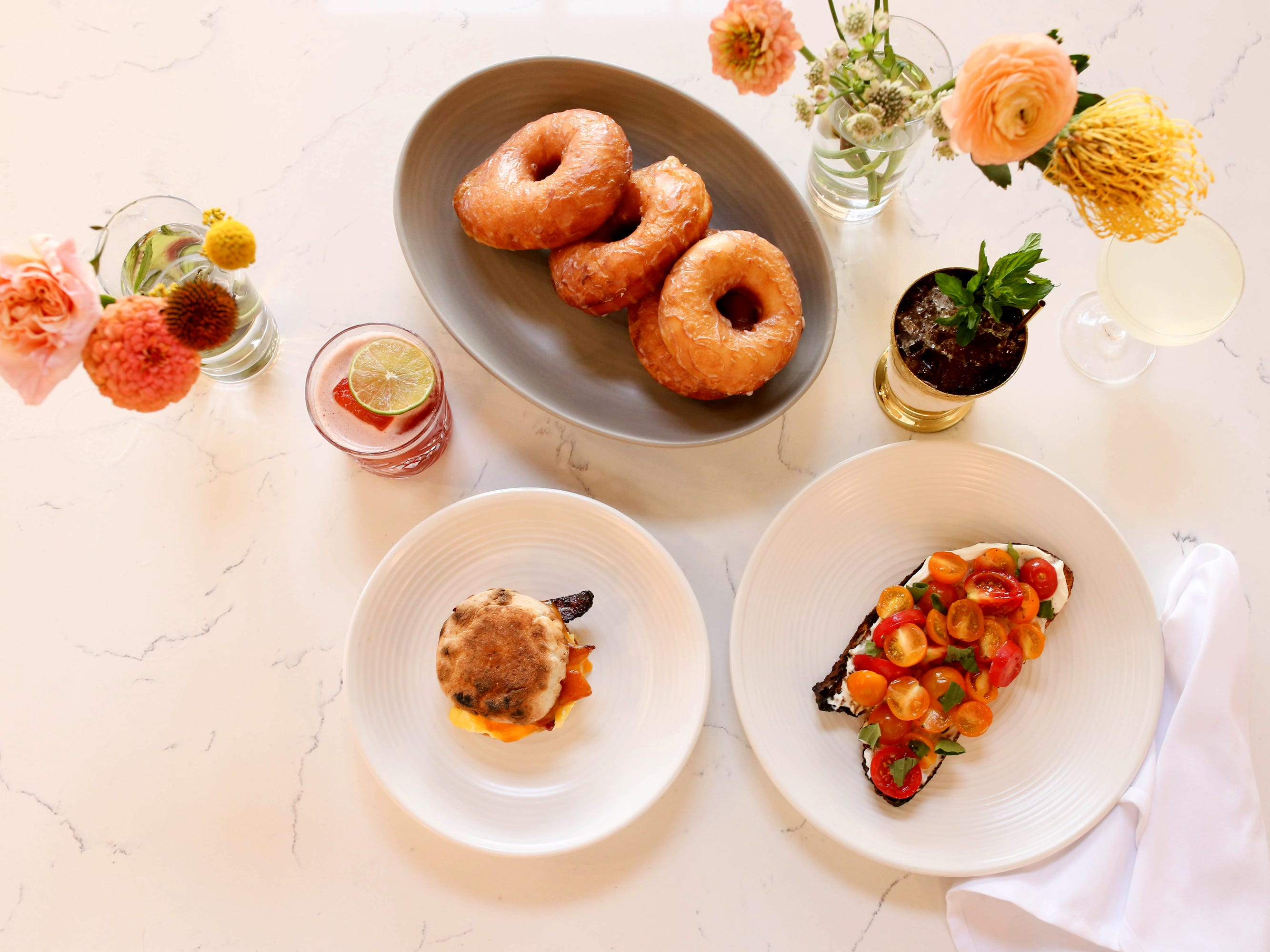 Vanilla glazed doughnuts, breakfast sandwich and beverages at Stay Golden restaurant and roastery.