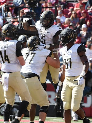 Vanderbilt running back Ke'Shawn Vaughn (5) celebrates with his team after scoring a touchdown in the second half of an NCAA college football game Saturday, Oct. 27, 2018, in Fayetteville, Ark.