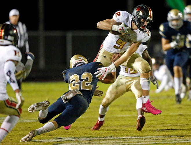 Ravenwood's Jake Briningstool (9) leaps as he's hit by Brian Pierce (22) of Independence during their game Friday, Oct. 26, 2018, in Thompsons Station, Tenn.