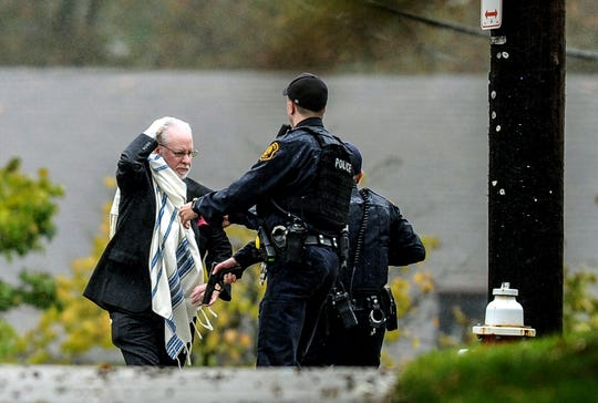 A man holds his head as he is escorted out of the Tree of Life Congregation by police following a shooting at the Pittsburg synagogue Saturday.