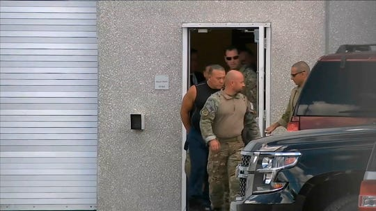This frame grab from video provided by WPLG-TV shows FBI agents escorting Cesar Sayoc, in sleeveless shirt, in Miramar, Fla., on Friday, Oct. 26, 2018. Sayoc is an amateur body builder and former male stripper, a loner with a long arrest record who showed little interest in politics until Donald Trump came along. On Friday, he was identified by authorities as the Florida man who put pipe bombs in small manila envelopes, affixed six stamps and sent them to some of Donald Trump's most prominent critics.