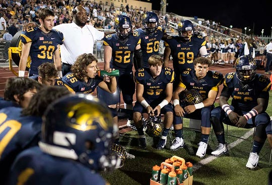 The Naples defense listens to a coach before the start of the game against Barron Collier at Naples High Friday night, October 26, 2018.