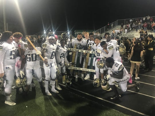 The Golden Gate High School football team celebrates winning the Battle for the Gate, 21-13, over rival Palmetto Ridge on Friday, Oct. 26, 2018.
