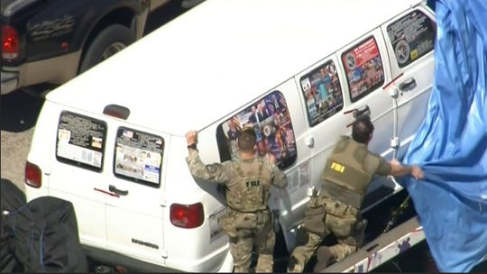 This frame grab from video provided by WPLG-TV shows FBI agents covering a van after the tarp fell off as it was transported from Plantation, Fla., on Friday, Oct. 26, 2018, that federal agents and police officers have been examining in connection with package bombs that were sent to high-profile critics of President Donald Trump. The van has several stickers on the windows, including American flags, decals with logos and text.