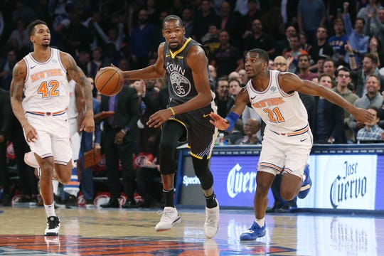 Oct 26, 2018; New York, NY, USA; Golden State Warriors forward Kevin Durant (35) controls the ball against New York Knicks forward Lance Thomas (42) and New York Knicks guard Damyean Dotson (21) during the second quarter at Madison Square Garden.