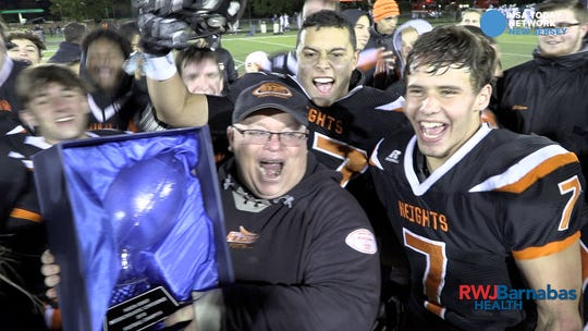 Hasbrouck Heights head coach Nick DelCalzo holds the trophy for winning the NJIC title after his team defeated Rutherford.