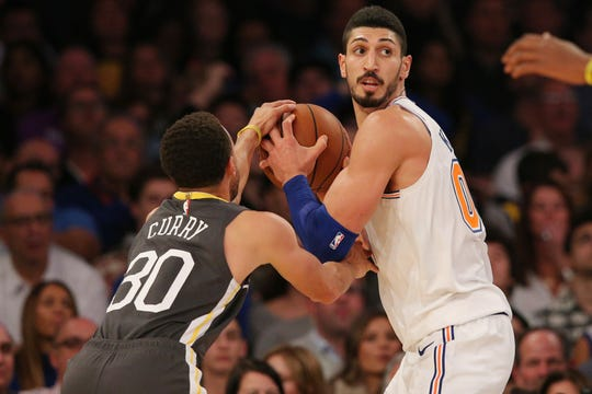 Oct 26, 2018; New York, NY, USA; New York Knicks center Enes Kanter (00) controls the ball against Golden State Warriors guard Stephen Curry (30) during the second quarter at Madison Square Garden.