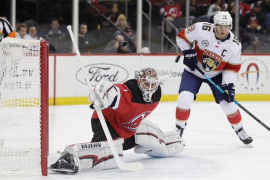 New Jersey Devils goaltender Keith Kinkaid (1) tries to block a shot from the Florida Panthers as Aleksander Barkov (16), of Finland, looks on during the first period of an NHL hockey game, Saturday, Oct. 27, 2018, in Newark, N.J.