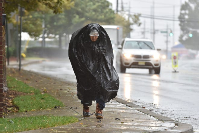 An unidentified person uses a plastic bag to shield from the rain and wind in Edgewater, NJ.