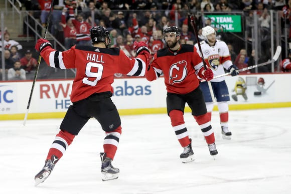 New Jersey Devils left wing Taylor Hall (9) celebrates his goal against the Florida Panthers with teammate Kyle Palmieri, right, during the second period of an NHL hockey game, Saturday, Oct. 27, 2018, in Newark, N.J.