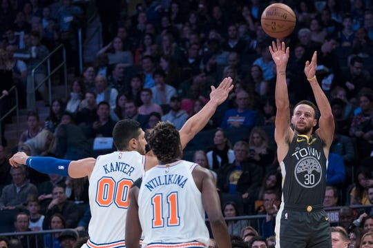 Golden State Warriors guard Stephen Curry (30) shoots a three-point basket past New York Knicks guard Frank Ntilikina (11) and center Enes Kanter (00)during the first half of an NBA basketball game, Friday, Oct. 26, 2018, at Madison Square Garden in New York.