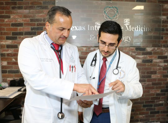 El Paso physician Oscar Aguilar, MD, looks over an EKG report with BCOM medical student Carlos Yeelot.