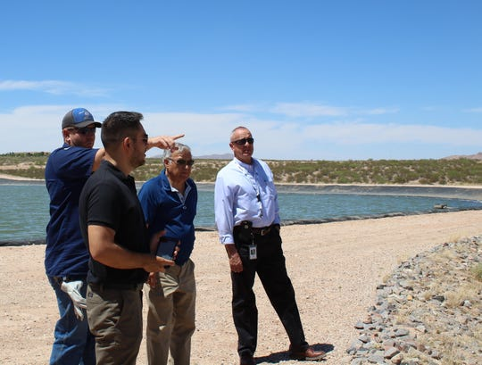 Ed Archuleta, LCU Board vice chairman, and Gabriel Vasquez, city councilor/LCU Board commissioner, join Utilities Director Jorge A. Garcia while Roy Hobbs, LCU equipment operator senior, explains how wastewater transfers from one holding pond to another at the West Mesa Industrial Park Wastewater Treatment Facility.
