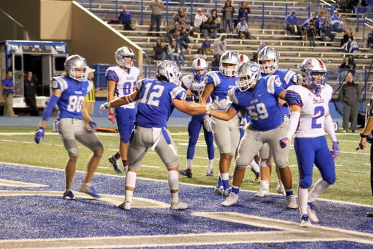 Carlsbad's Kyle Daniell (12) celebrates scoring a touchdown with teammate Crimson Mckenzie (59) in the third quarter of Friday's game against Las Cruces.