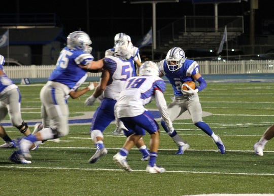 Carlsbad's Taylor Miterko (75) creates running room for Tate Collins (2) against Las Cruces. Collins scored the first touchdown of the game.