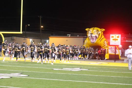 The Alamogordo Tigers rush valiantly back onto the field after a difficult first half of the match-up against the Roswell Coyotes.