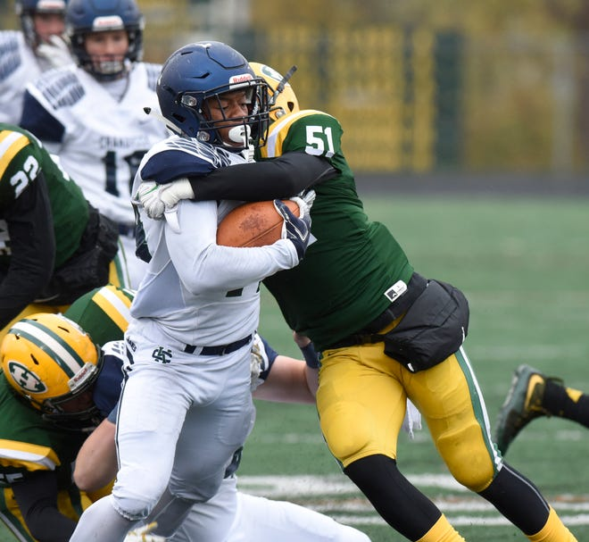 Cranbrook RB Tariq Muhammad (14) is wrapped up by Farmington Harrison's Andrew Dooley (51) during the Division 4 predistirct game Oct. 27, 2018.