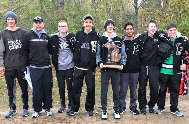 The Plymouth boys cross country team holds the Division 1-Regional 6 trophy at Willow Metropark.