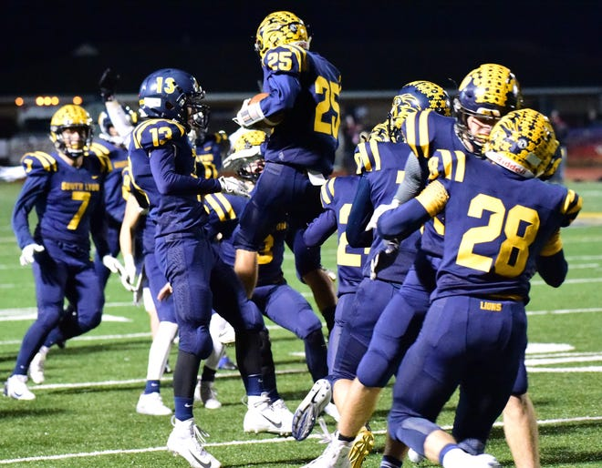 Junior defender Jake Newman (25) is mobbed by his teammates after intercepting a Dexter pass in overtime to secure South Lyon's first playoff victory in seven years.