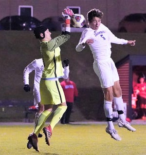 Catholic Central's John Willemsen (right) goes up for the header in front of Grand Blanc goalkeeper