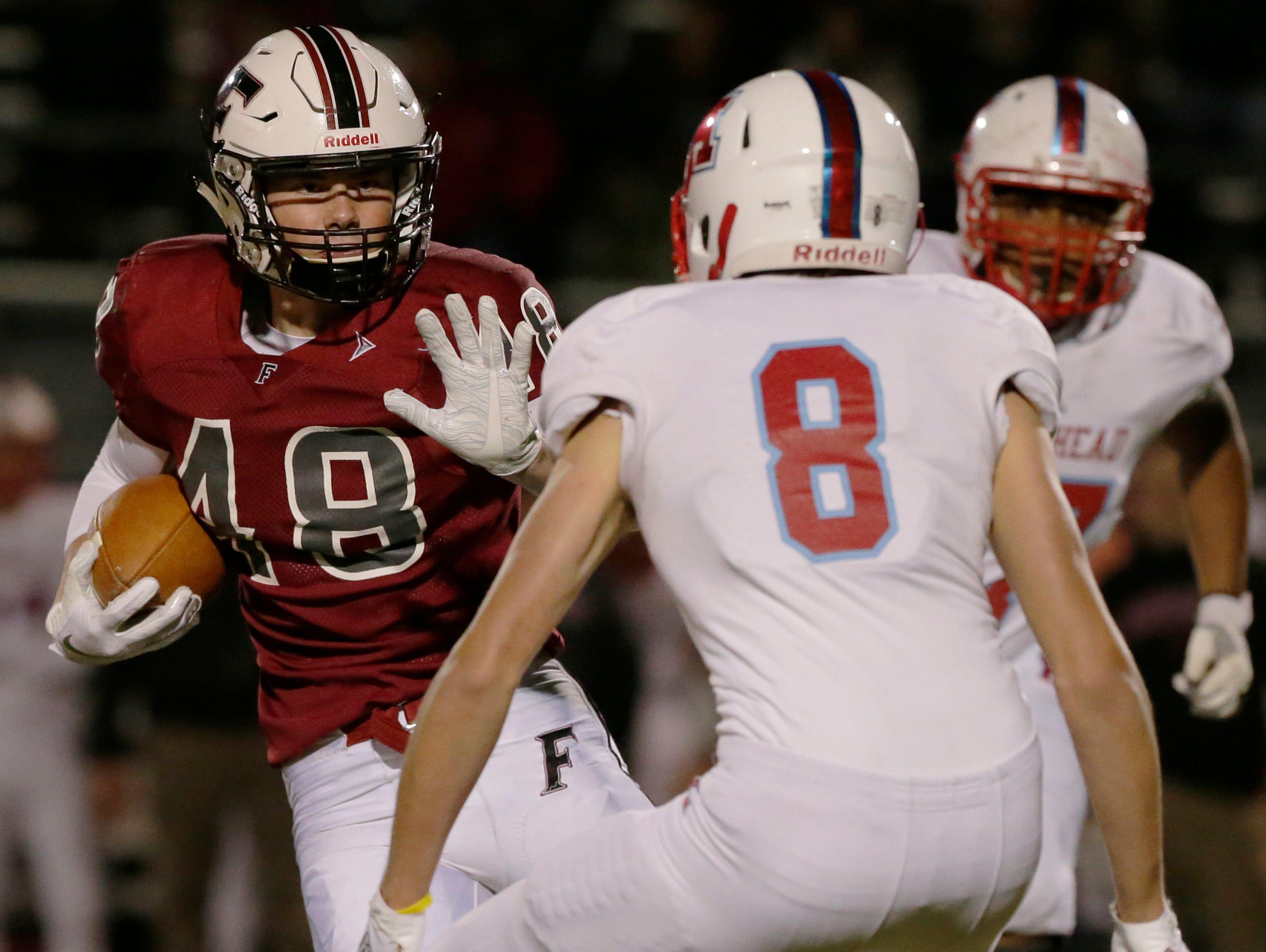 Fond du Lac's Adam Hopper runs the ball against Arrowhead's Jonathan Witter during their game.  Fond du Lac Cardinals played Arrowhead Warhawks in WIAA football playoff sectionals, Friday, Oct. 26, 2018, at Fruth Field in Fond du Lac.   Fond du Lac won 28 - 22.Joe Sienkiewicz/USA Today NETWORK-Wisconsin