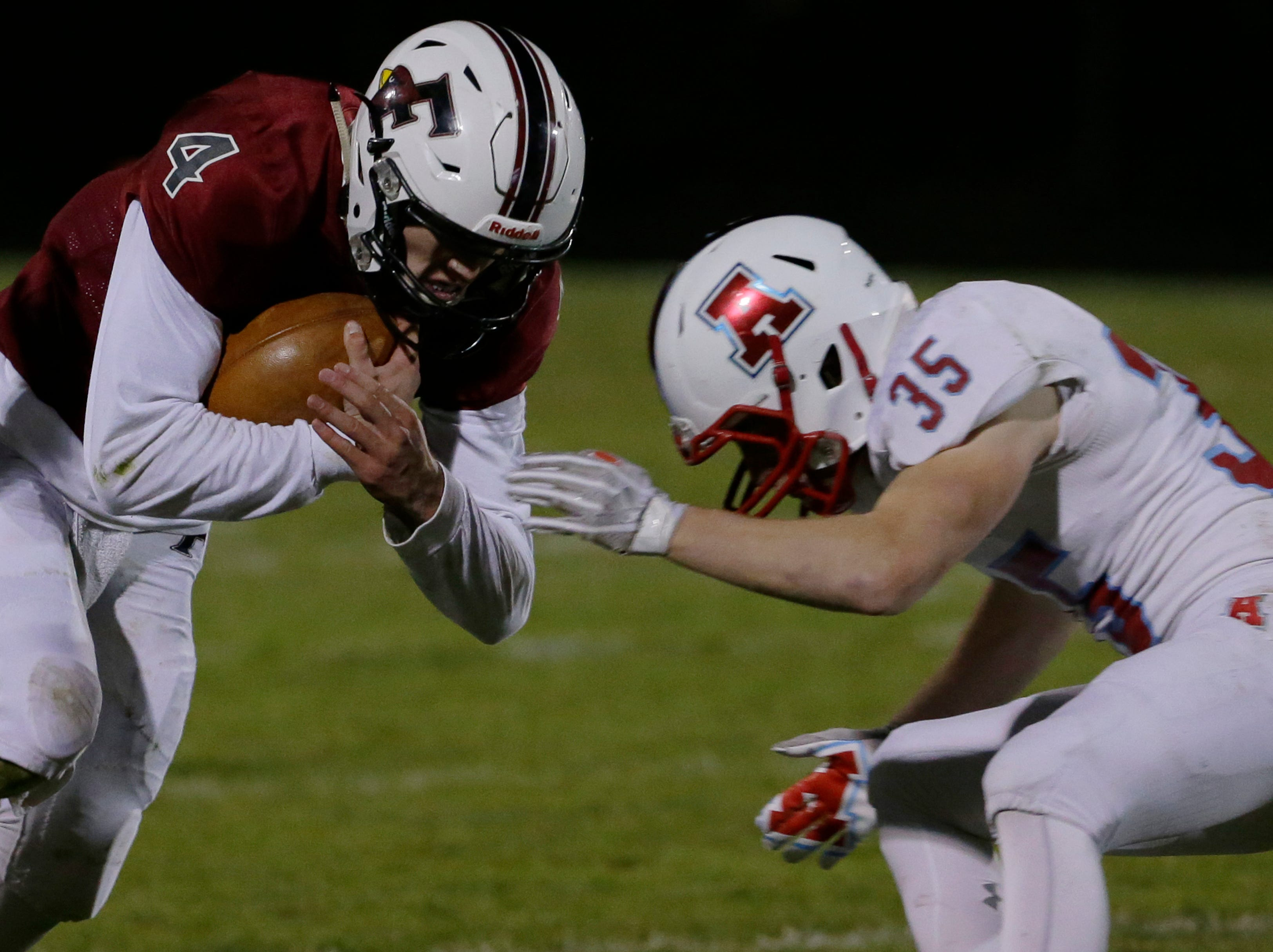 Fond du Lac's Carson Raddatz runs the ball at Arrowhead's Colton Borkowicz during the game.  Fond du Lac Cardinals played Arrowhead Warhawks in WIAA football playoff sectionals, Friday, Oct. 26, 2018, at Fruth Field in Fond du Lac.    Fond du Lac won 28 - 22.Joe Sienkiewicz/USA Today NETWORK-Wisconsin