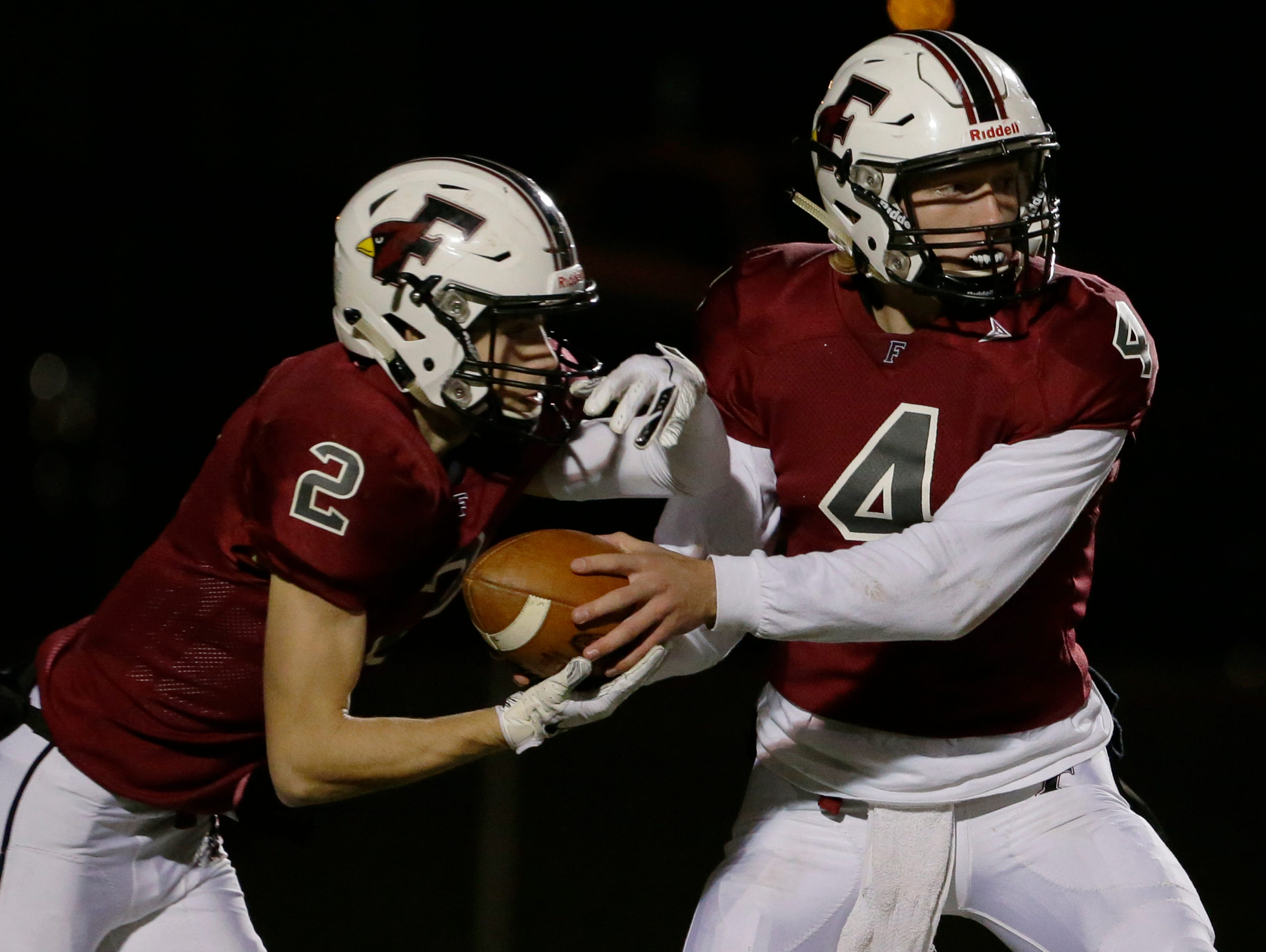 Fond du Lac's Carson Raddatz hands off to Eben Sauer during their game.  Fond du Lac Cardinals played Arrowhead Warhawks in WIAA football playoff sectionals, Friday, Oct. 26, 2018, at Fruth Field in Fond du Lac.  Fond du Lac won 28 - 22.Joe Sienkiewicz/USA Today NETWORK-Wisconsin