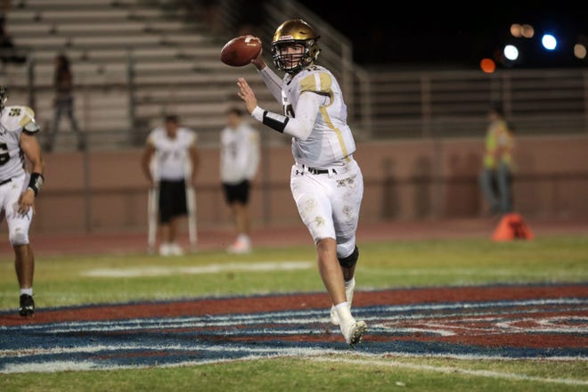 Xavier Prep's Brad McClure rolls out to pass during the Saints win over La Quinta on Friday. The Saints have qualified for the playoffs for the first time.