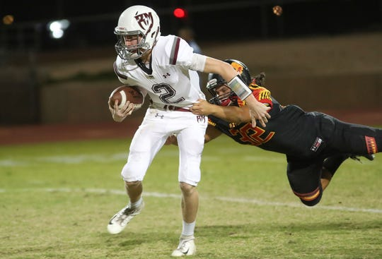 Rancho Mirage quarterback Ty Hershberger tries to escape Nathan Brito-Aguilar of Palm Desert, October 26, 2018.