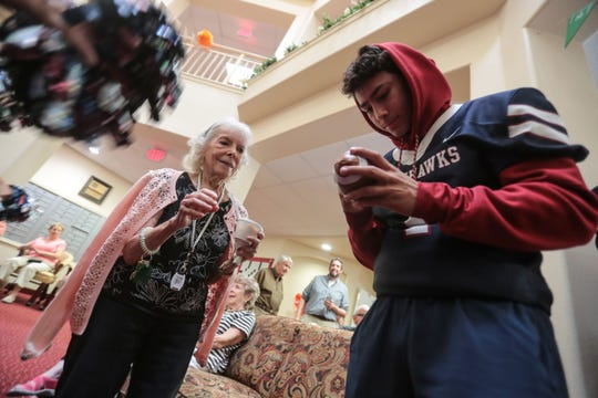 Marcus McAvoy signs Charlotte Roberts' toy football at The Palms at La Quinta Independent Living Facility on Thursday, October 25, 2018 in La Quinta during a La Quinta cheer-squad and football team a pep rally for the seniors.