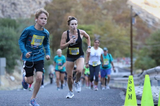 First place female runner Amanda Sellers, center, nears the finish line in the 33rd annual Tram Road Challenge in Palm Springs on Saturday, October 27, 2018.