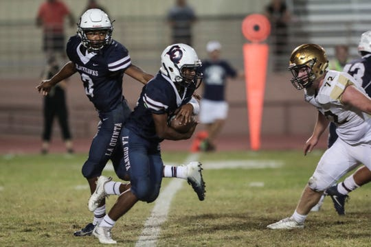 La Quinta quarterback Christian Egson hands the ball to Michael Smith during play against Xavier Prep on Friday, October 26, 2018 in La Quinta.
