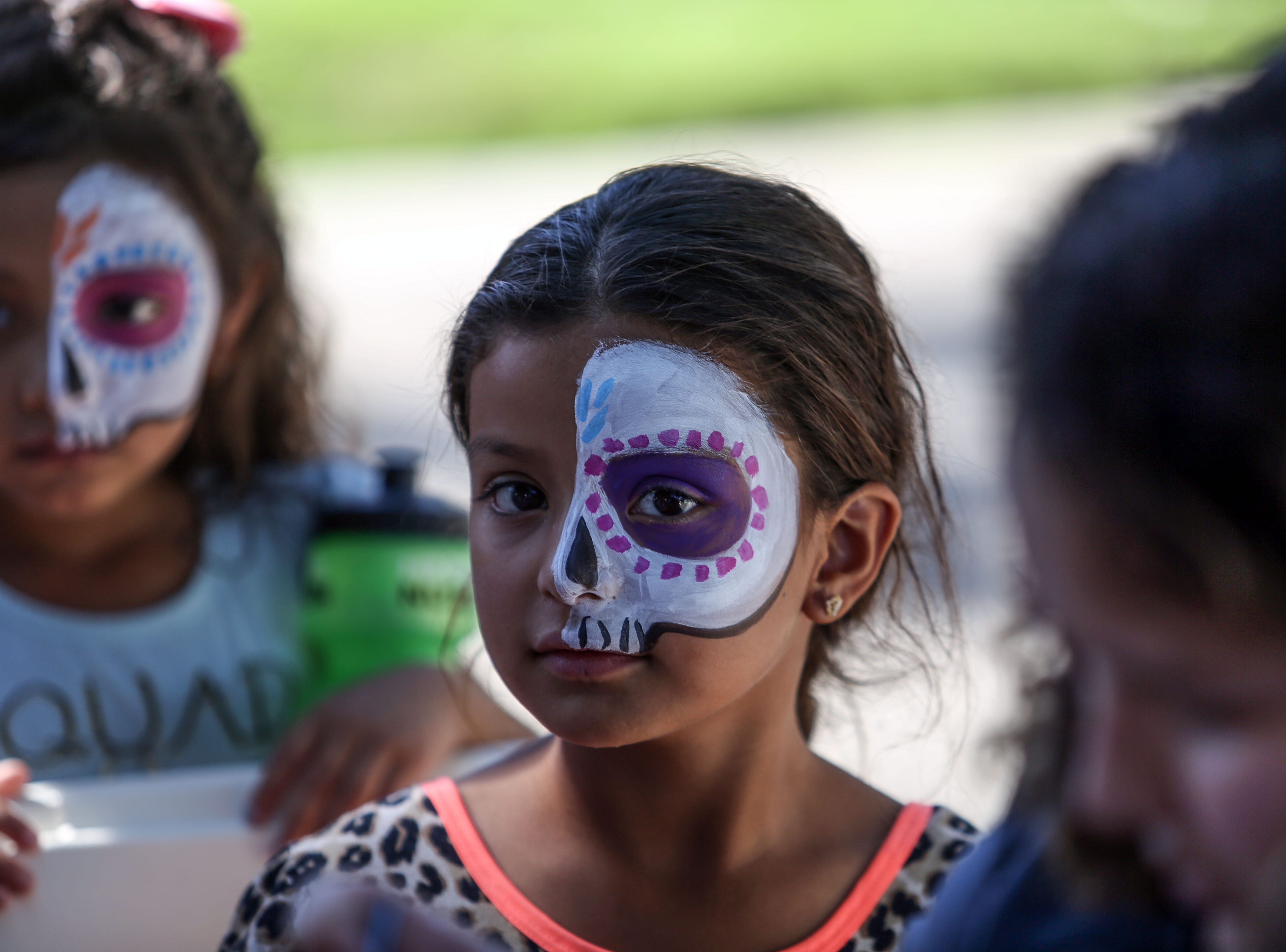 Carol Arias, 7, center, and Daisy Villegas, 4, have their faces painted during Cathedral City's annual Dia de los Muertos celebration at Desert Memorial Park cemetery on Saturday, October 27, 2018.