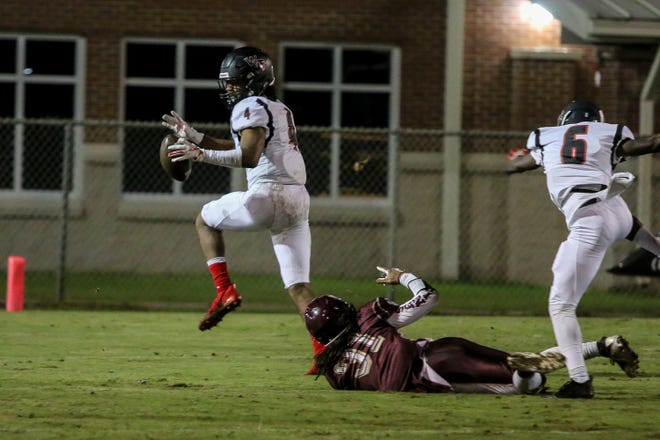 West Florida Tech's Antarrius Moultrie (4) picks up a blocked PHS punt and runs in for a touchdown in the District 1-5A matchup at Pensacola High School on Friday, October 26, 2018.