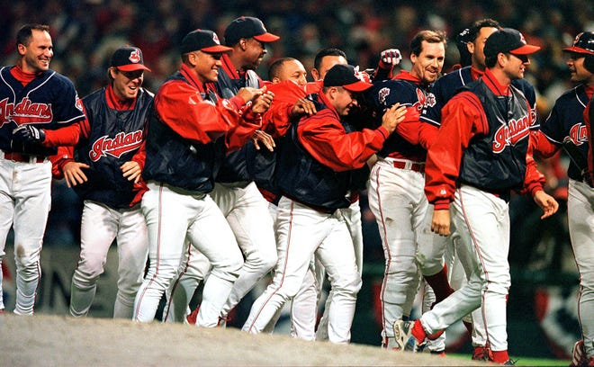 CLEVELAND, :  Cleveland Indians third baseman Travis Fryman (4th R,without hat) is joined by teammates to celebrate his game-winning single hit off of Red Sox pitcher Rich Garces in the ninth inning of game one of the American League Division Series playoff game 06 October 1999 at Jacobs Field in Cleveland, OH. The Indians defeated the Red Sox 3-2.  AFP PHOTO David MAXWELL (Photo credit should read DAVID MAXWELL/AFP/Getty Images)