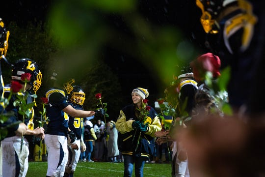 Miriam Worley receives roses from Littlestown players before being proposed to by her boyfriend, Littlestown's Malachi Fodor (70), after winning a game against Fairfield, Friday, Oct. 26, 2018, at Littlestown's Memorial Stadium.
