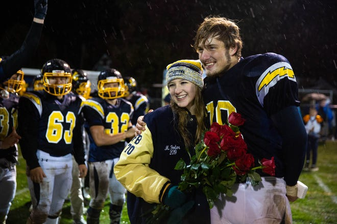Littlestown's Malachi Fodor (70) poses for a photo with his girlfriend, Miriam Worley, after Fodor proposed to her following his win against Fairfield, Friday, Oct. 26, 2018, at Littlestown's Memorial Stadium.