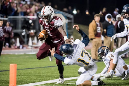 Gettysburg's Ammon Robinson pushes off Greencastle-Antrim's Antwoine Carter before being knocked out of bounds near the end zone on Friday, October 26, 2018. The Warriors won 50-0 and Robinson surpassed the school's single-season rushing record of 1,365 yards which was set by Jason Shelton (1993).