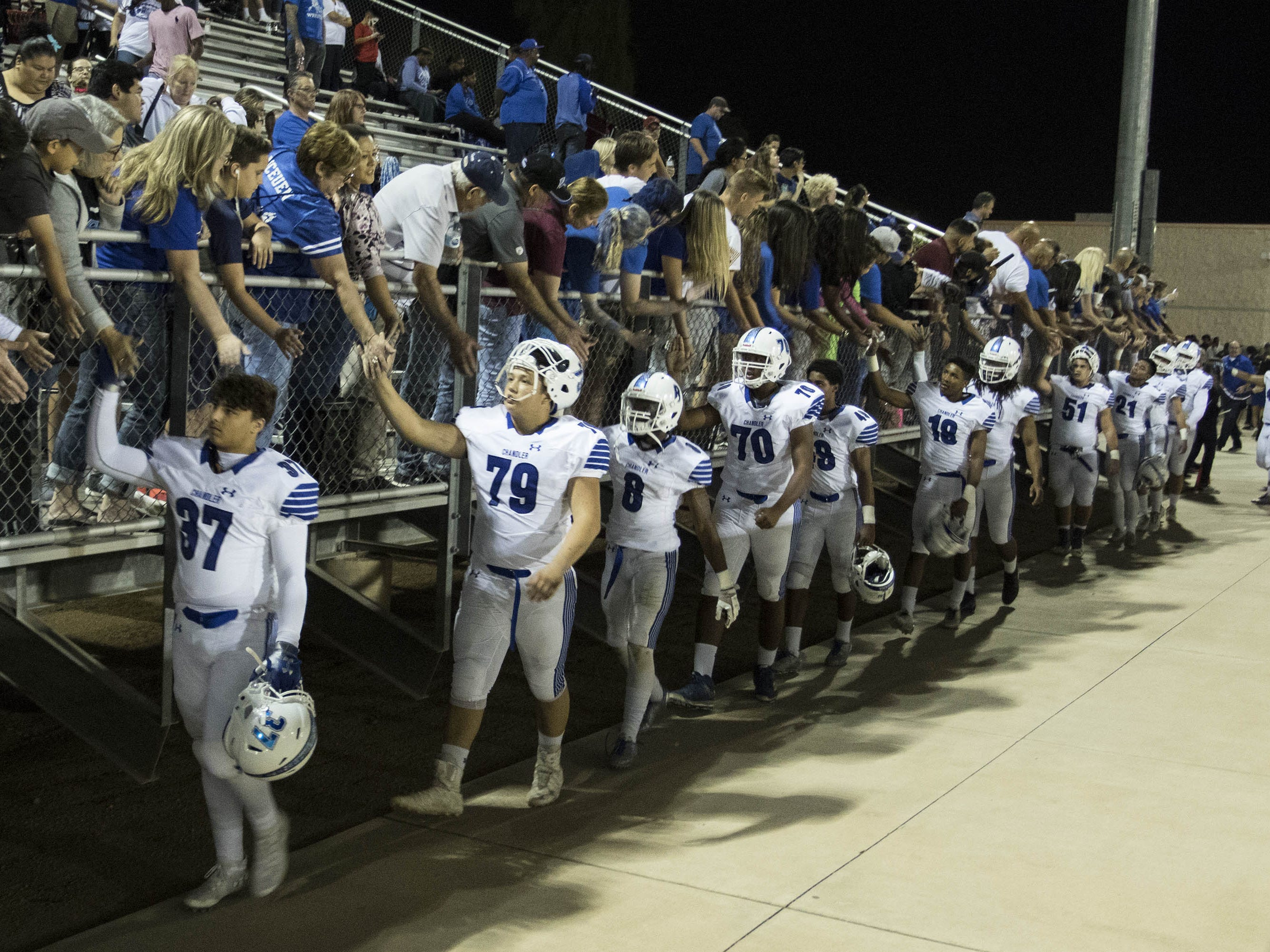 Chandler players get and give high-fives to fans after their 49-7 win over crosstown rival Hamilton, Friday, Oct. 26, 2018. #azhsfb