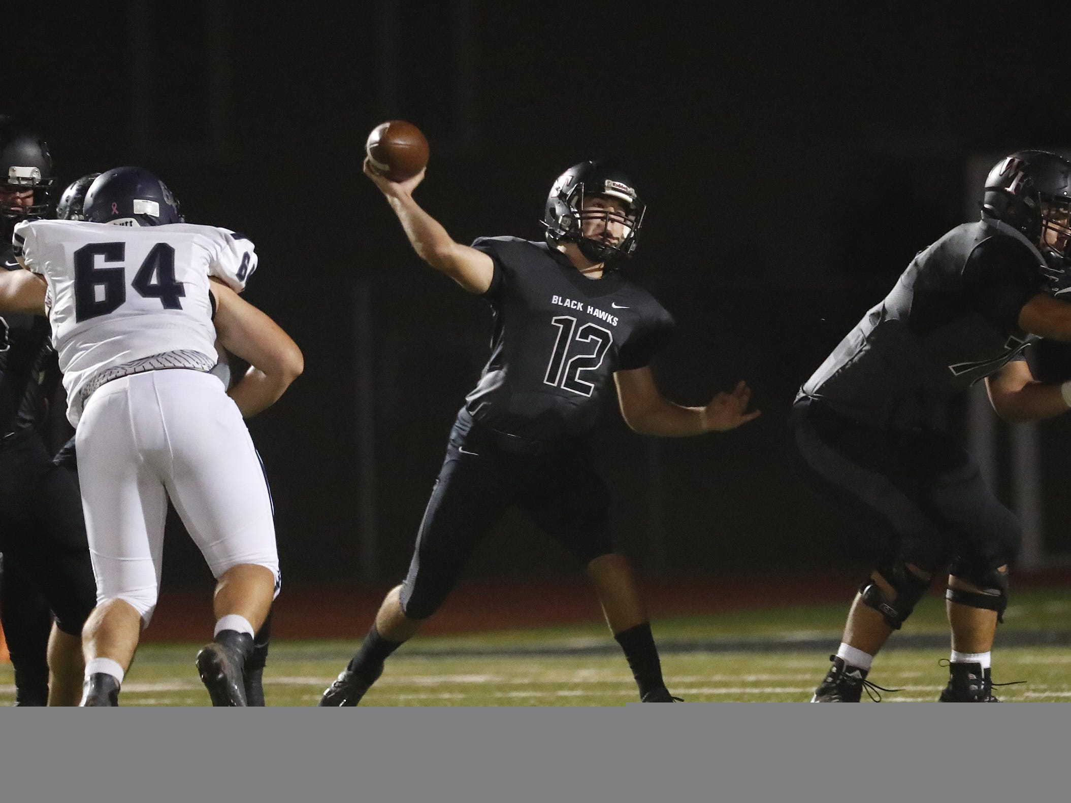 Williams Field's Zack Shepherd (12) throws a pass under pressure from Higley's Jackson Solomon (64) during the first half at Williams Field High School in Gilbert, Ariz. on October 26, 2018.