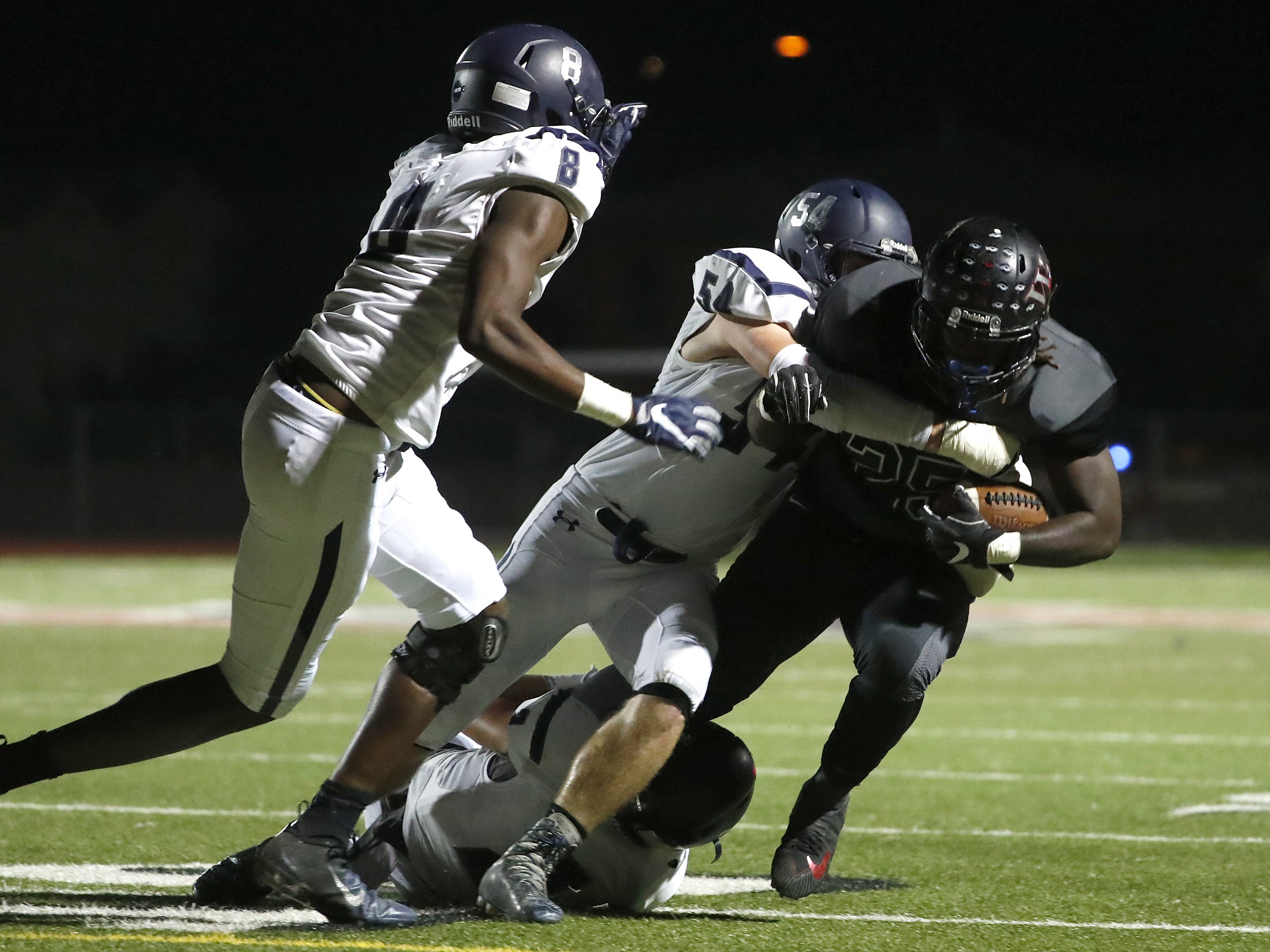 Higley's Dylan Pedersen (54) tackles Williams Field's Jaden Thompson (25) during the first half at Williams Field High School in Gilbert, Ariz. on October 26, 2018.