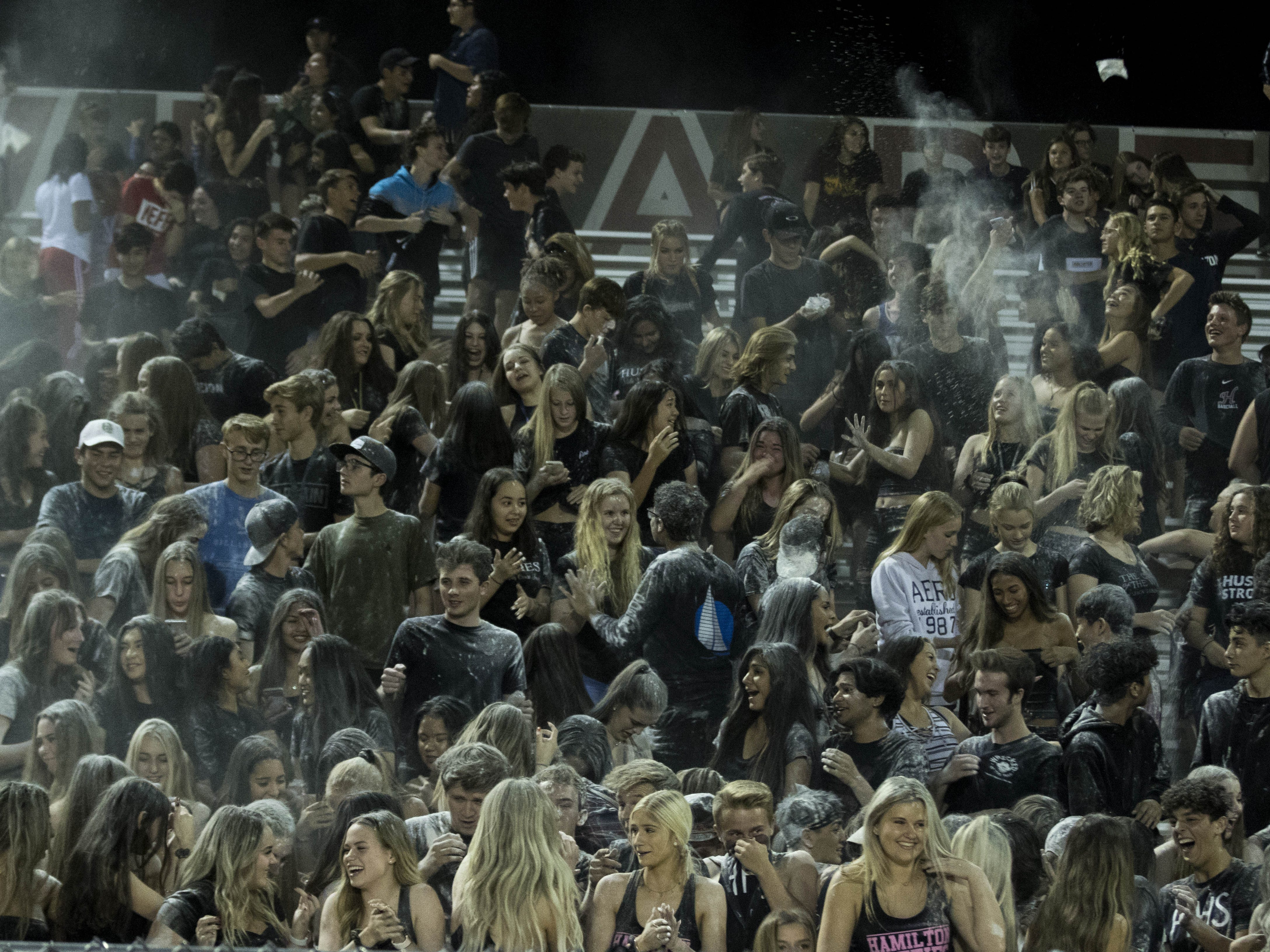 Hamilton High School students endure the aftermath of a powder shower before their game against crosstown rivals the Chandler Wolves in Chandler, Friday, Oct. 26, 2018. #azhsfb