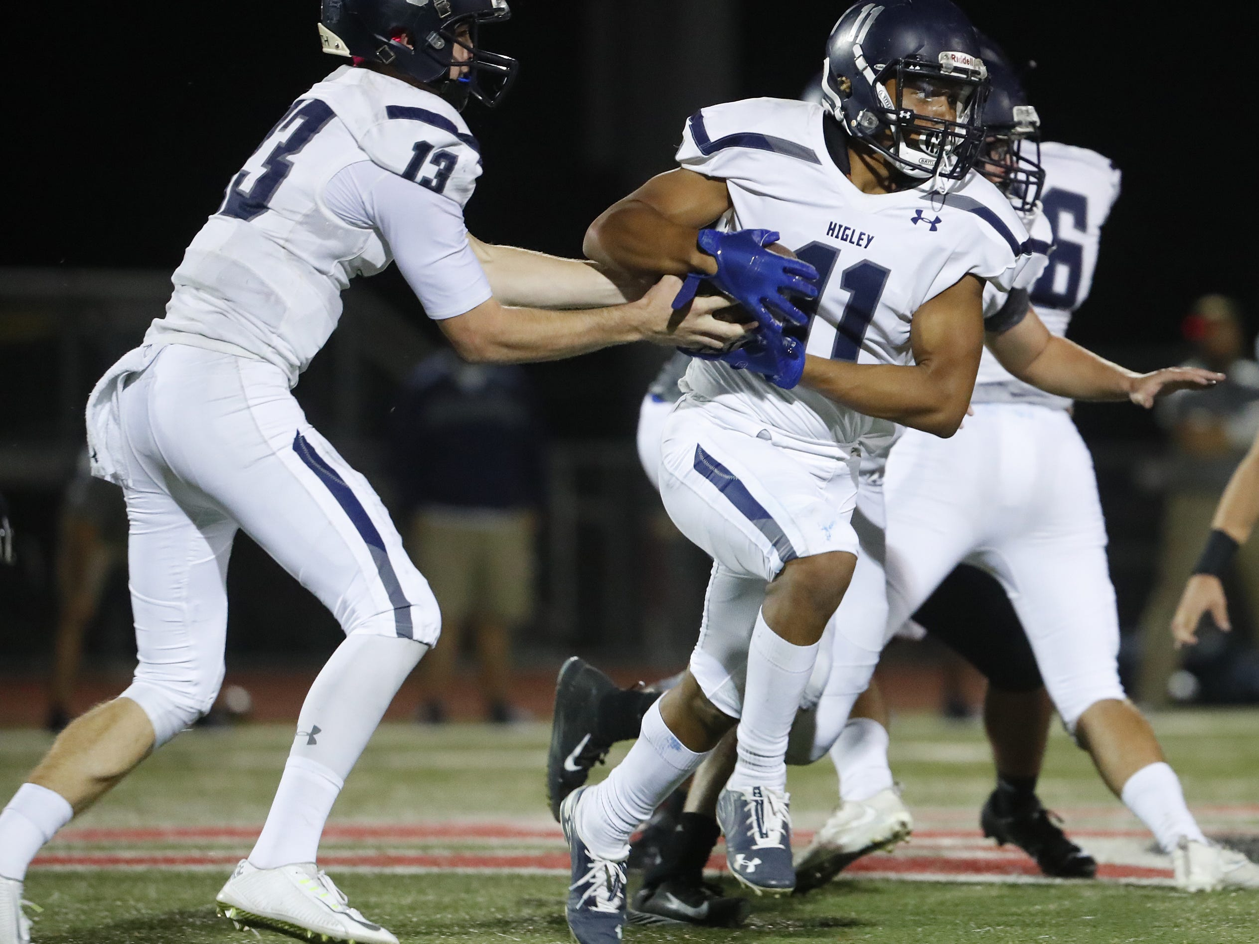 Higley's Spencer Brasch (13) hands the ball off to Isaiah Eastman (11) against Williams Field at Williams Field High School in Gilbert, Ariz. on October 26, 2018.