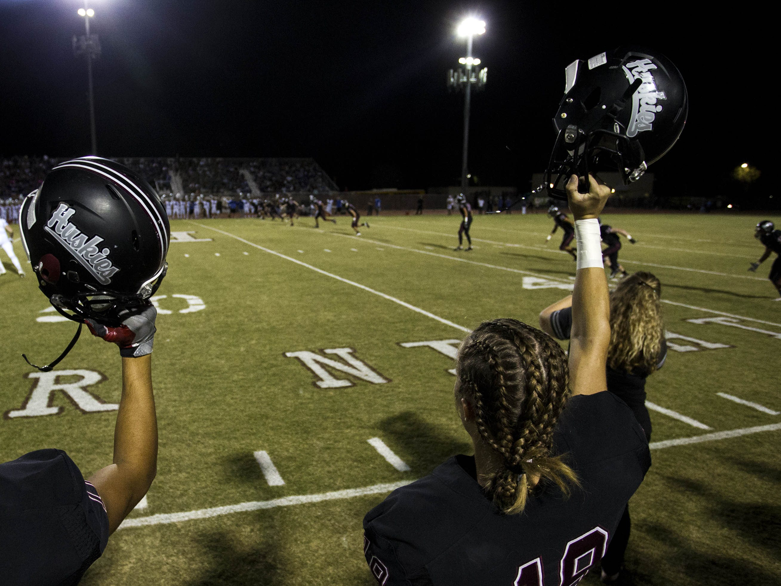 Hamilton players hold their helmets up as the opening game kickoff gets underway with Chandler in Chandler, Friday, Oct. 26, 2018. #azhsfb